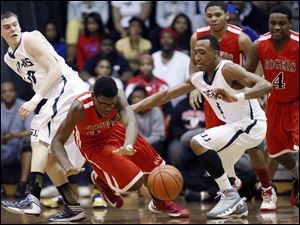 St. John's Jesuit's Austin Gardner (10) and Anthony Glover (4) scramble for the loose ball.