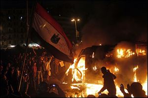 Egyptian protesters use camera phones to capture a burning state security armored vehicle that demonstrators commandeered during clashes with security forces nearby and brought to Tahrir Square and set it alight, in Cairo, Egypt, Monday.