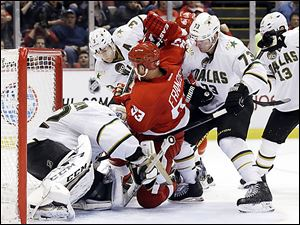 The Red Wings' Johan Franzen is tied up between the Stars' Stephane Robidas, Michael Ryder, and goalie Kari Lehtonen during the second period.