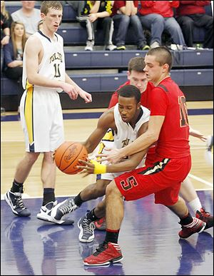 Toledo Christian's Melvin Thomas, center, is guarded by Cardinal Stritch's Joey Cousino, who scored 11 of his 16 points during a 16-5 run in the second quarter.