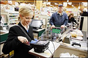 Cherie McHue of Toledo uses her credit card to pay for purchases Tuesday at The Anderson's in Toledo. No extra fee was charged.
