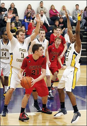 Toledo Christian defenders surround Cardinal Stritch's Austin Adams during the second half. TC sank 13 of 14 free throws in the fourth quarter to prevail, winning its 13th straight game.