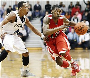 Rogers' Clemmye Owens, right, drives past  St. John's player Anthony Glover. Owens scored 19 points for the Rams while Glover had 10 for St. John's.