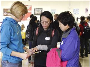 Sixth grade technology teacher Jackie Derr, left, speaks with Liping Niu, middle, and English teacher, and physics teacher Jinglan Wei.