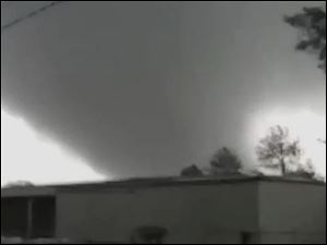 In this image made from video and released by WSB TV in Atlanta, a tornado moves through the town of Adairsville, Ga. Today.