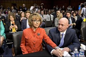 Former Arizona Rep. Gabrielle Giffords, who was seriously injured in the mass shooting that killed six people in Tucson, Ariz. two years ago, sits with her husband, Mark Kelly, right, a retired astronaut, on Capitol Hill in Washington.