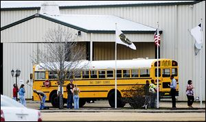 Residents look over the school bus where a shooting occurred near Destiny Church along U.S. 231, just north of Midland City, Ala. on Tuesday.