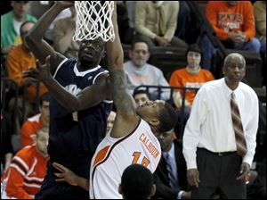 Akron's Demetrius Treadwell shoots over BGSU's A'uston Calhoun during their game at the Stroh Center at BGSU in Bowling Green.