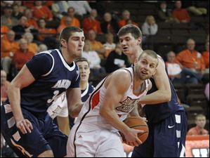 BGSU's Luke Kraus dribbles through Akron's Pat Forsythe, left, and Reggie McAdams.