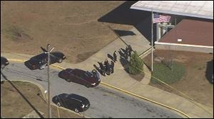 Authorities investigate the scene of a school shooting in Atlanta.
