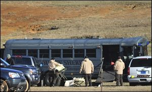 Law enforcement personnel load provisions into a bus during the third day of a hostage crisis involving a 5-year-old boy, in Midland City, Ala.