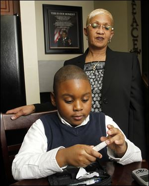 E'zion Watson, 7, checks his blood sugar with his grandmother, Dawn Watson, by his side in their Toledo home.