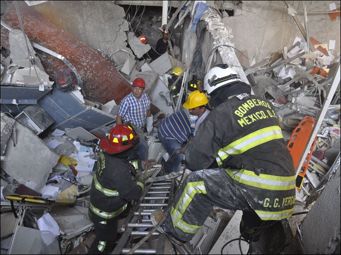 Firefighters belonging to the Tacubaya sector and workers dig for survivors after an explosion at an adjacent building to the executive tower of Mexico's state-owned oil company PEMEX today in Mexico City.