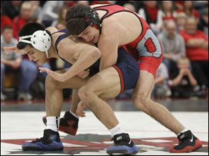 Ohio State University wrestler Nikko Triggas, top, tries to control University of Illinois wrestler Jesse Delgado.