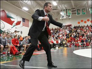 Ohio State University head coach Tom Ryan urges Kenny Courts as he wrestles against University of Illinois' Mario Gonzalez.