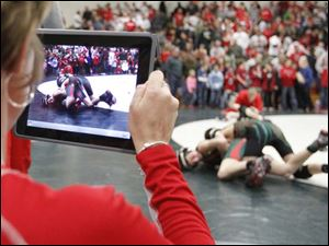 A fan records a match between Oak Harbor Elementary students during half time.