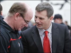 Oak Harbor High School wrestling coach George Berman, left, jokes with Ohio State University head coach Tom Ryan before the Buckeyes wrestle the University of Illinois.