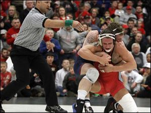 Ohio State University wrestler Cody Magrum battles to escape from University of Illinois wrestler Tony Dallago.