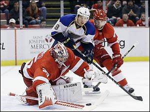 Red Wings goalie Jimmy Howard reaches for the puck in front of St. Louis' Jaden Schwartz and Detroit defenseman Jakub Kindl.