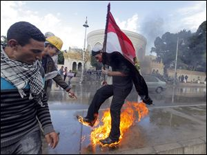 An Egyptian protester tries to escape from fire after he burned an anti-Mohammed Morsi banner in front of the presidential palace in Cairo, Egypt.