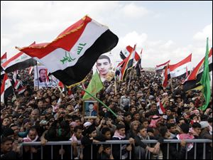 Iraqis chant anti-government slogans as they wave national flags and hold posters of slain protesters in Fallujah, 40 miles west of Baghdad, Iraq.