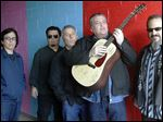 Members of the band Los Lobos, from left, Louie Perez, Cesar Rosas, Conrad Lozano, David Hidalgo holding a guitar, and Steve Berlin posing for a photograph, in Los Angeles.
