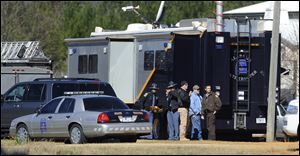 Law officers stand beside the Alabama State trooper mobile command post at the Dale County hostage scene in Midland City, Ala.