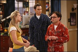 Penny (Kaley Cuoco, left) is surprised when she finds Leonard (Johnny Galecki, right) and Sheldon (Jim Parsons, center) competing for the attention of a famous female physicist, on The Big Bang Theory.