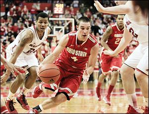 Ohio State's Aaron Craft, center, drives between Nebraska's Dylan Talley, left, and Andre Almeida, right, in the second half. Craft finished the contest with 14 points.