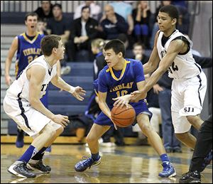Findlay's Grant Niswander, center, is pressured by St. John's Jesuit's Austin Gardner, left, and Marc Loving during Friday's game at St. John's. Gardner had 15 points while Loving added 12.