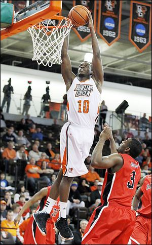 Bowling Green's  Craig Sealey dunks over Ball State's Marcus Posley during Saturday's game at BGSU. The Falcons came away with a 70-59 victory.