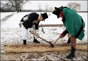 Re-enactors Dick Micka, left, of Monroe and Kenneth Roberts of St. Clair Shores, Mich., cut logs to build a block house.