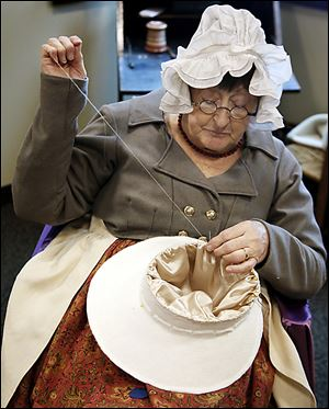 Re-enactor Jean Roberts of St. Clair Shores, Mich., sews a hat as part of the festivities.