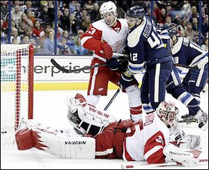 The Blue Jackets' Artem Anisimov scores against the Red Wings' Kent Huskins (3) and Jimmy Howard in the second period in Columbus. Anisimov scored twice.