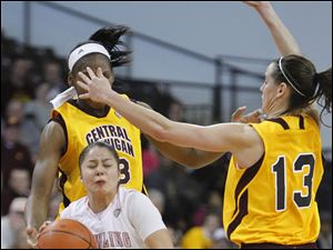 Bowling Green's Katrina Salinas is knocked down by Central Michigan players Brandie Baker, left, and Jessica Schroll, right.