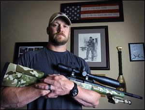 "Chris Kyle, former Navy SEAL and author of the book ""American Sniper,"" poses in Midlothian, Texas. Eddie Ray Routh of Lancaster was arraigned early Sunday in the deaths of Kyle, 38, and Chad Littlefield, 35, at a shooting range at Rough Creek Lodge, Texas, about 50 miles southwest of Fort Worth. He was being held on one charge of capital murder and two charges of murder."