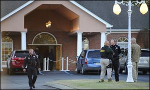 Law enforcement personnel wait outside the funeral home, Saturday, as people pay their respects to Charles Albert