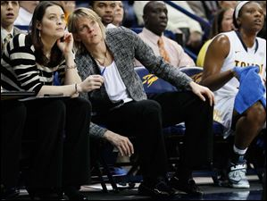 University of Toledo women's associate head basketball coach Vicki Hall, leaning, center, watches from the bench during the Rockets' game.