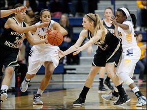 Western Michigan's Alex Morton, center, tries to pass to teammate Corie Buchanan, left, as Toledo's Inma Zanoguera,  tries to steal the ball. Toledo defender at right is Andola Dortch.