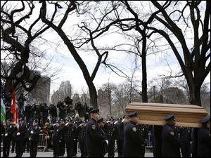 A casket containing the body of former New York City Mayor Ed Koch is loaded into a hearse while city employees, politicians, media watch after his funeral in New York.