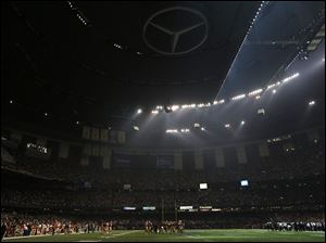 Players huddle on the field during a Superdome power outage in the second half of Super Bowl XLVII, Sunday, in New Orleans.