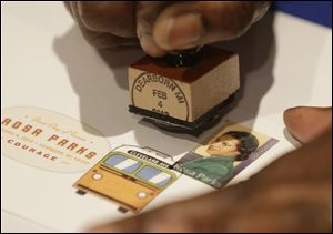 A postal service employee prepares to cancel the Rosa Parks' 100th birthday commemorative postage stamp at The Henry Ford museum in Dearborn, Mich.