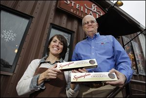 Nancy Bontrager and Dean L. Spangler of the Spangler Candy Co., with boxes of hand crafted peanut clusters she is making for the company at her Stella Leona artisan chocolates in Pettisville.