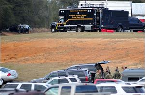 Federal and local law enforcement officers gather at their trucks after the hostage crisis ended in Midland City, Ala.  Officials say they stormed a bunker in Alabama to rescue a 5-year-old child being held hostage there after his abductor was seen with a gun.