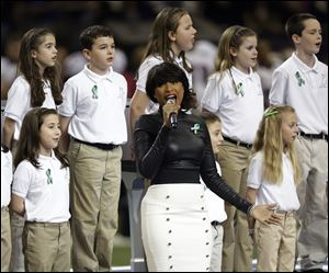 Jennifer Hudson, center, sings 'America the Beautiful' with the 26-member Sandy Hook Elementary School chorus. It was an emotional performance that had some players on the sideline on the verge of tears.
