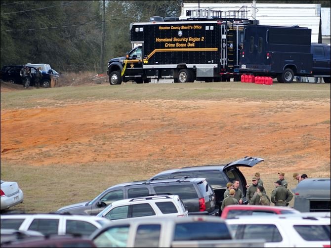 School Bus Driver Shot gun Federal and local law enforcement officers gather at their trucks after the hostage crisis ended in Midland City, Ala.  Officials say they stormed a bunker in Alabama to rescue a 5-year-old child being held hostage there after his abductor was seen with a gun.