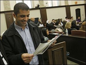 Ehab Abouadi smiles as he takes a look at his papers after being sworn in as an American citizen.