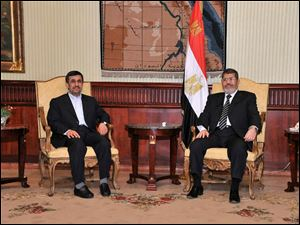 Iran's President Mahmoud Ahmadinejad, left, and Egyptian President Mohammed Morsi, right, pose for photographers in Cairo, today.