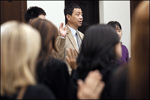 Kevin Yu, center, formerly of the United Kingdom, is among 30 immigrants who became American citizens in a ceremony in U.S. District Court in Toledo.  Another was Guillermo Vidales Gutierrez, who told about his 20-year path to citizenship on Tuesday.