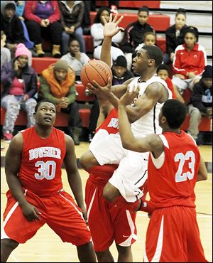 Rogers' Clemmye Owens drives past Bowsher's  Mark Washington (30) and Nate Allen during the second half. Owens scored 21 points for the 11-6 Rams.